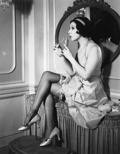 Woman sitting on a vanity smelling perfume from flacon